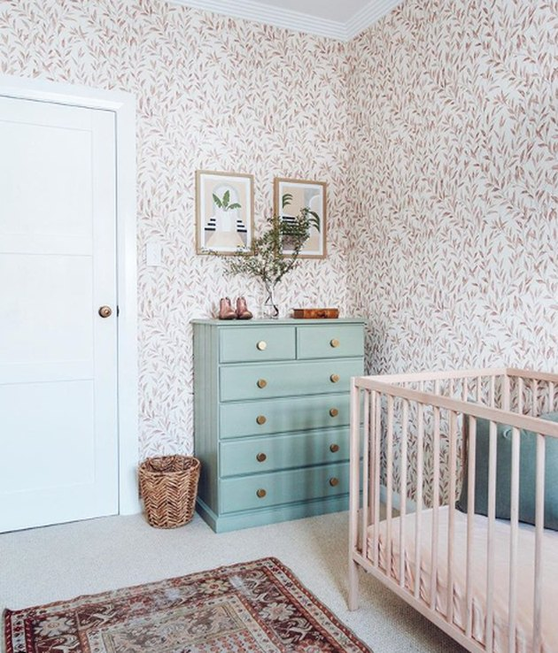 bohemian baby nursery idea with olive branch wallpaper, mint dresser, and natural crib