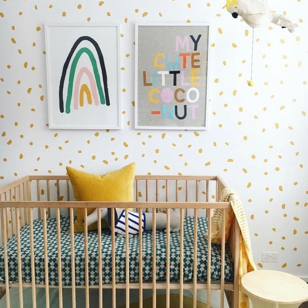 yellow nursery idea with polka dot inspired wallpaper and framed artwork on walls