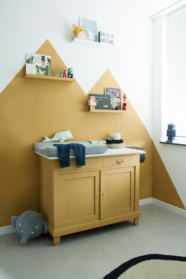 yellow nursery idea with color blocked mountains painted on wall and cabinet and shelves painted in same color