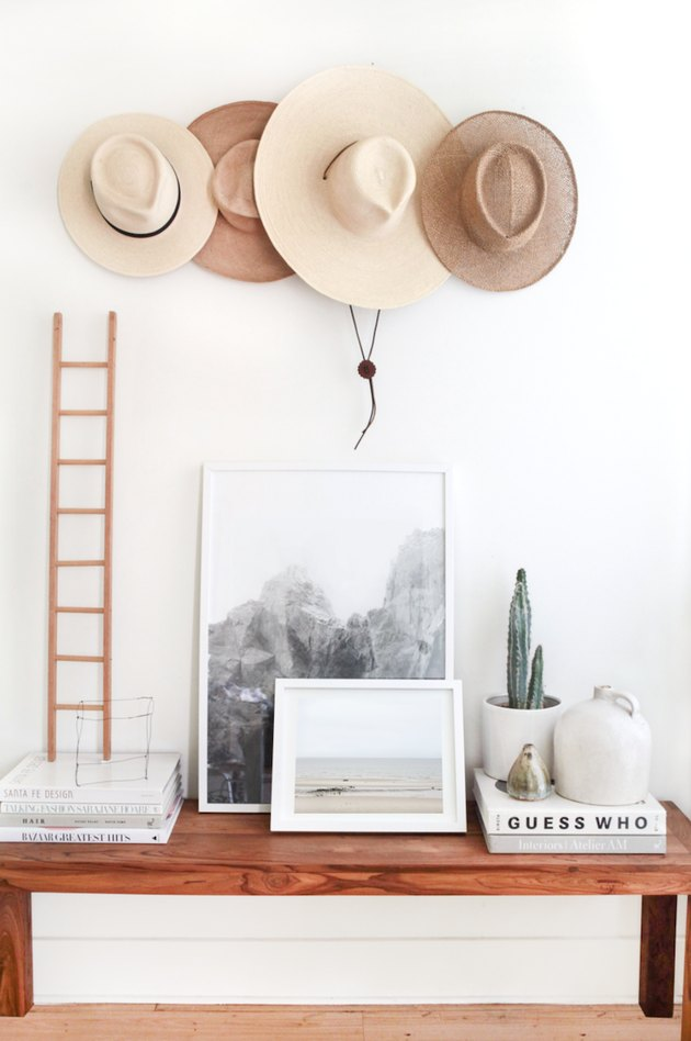 hats hung on wall above decorative table