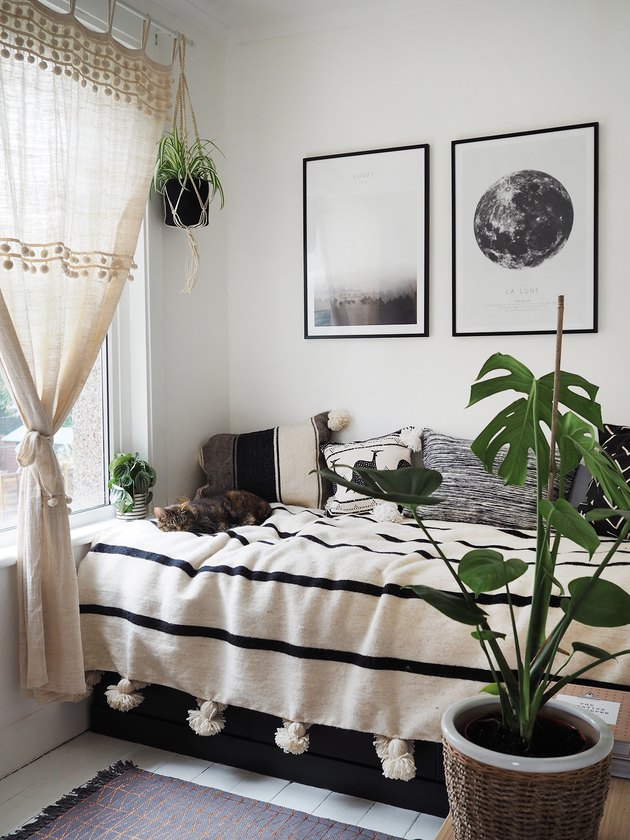 small bedroom idea with corner bed near window and potted plants