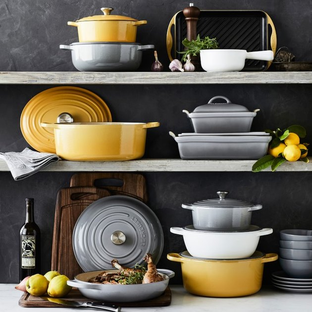 grey, yellow, and white Le Creuset cookware on shelves
