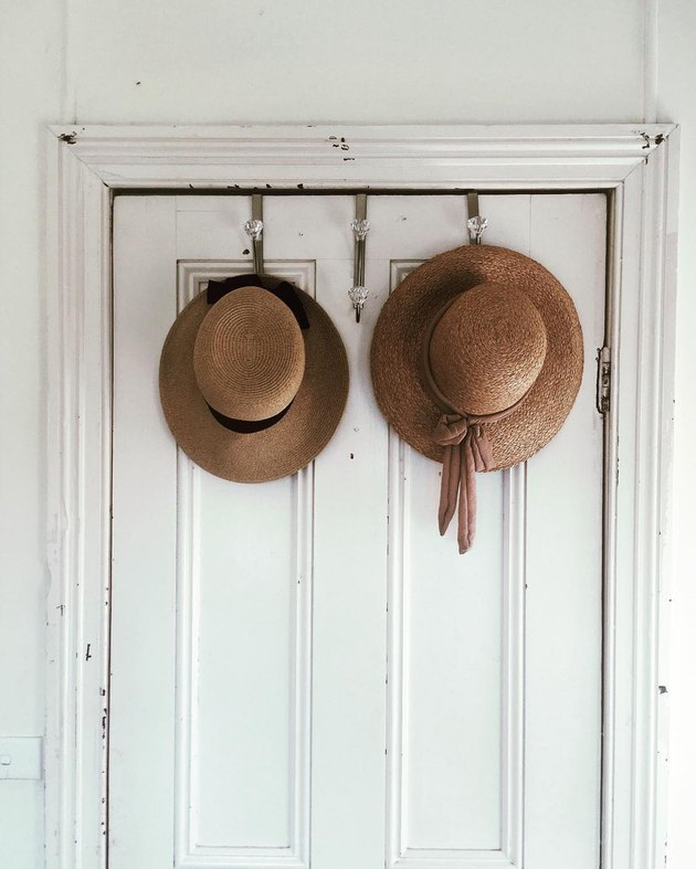 hats hung on the back of a door