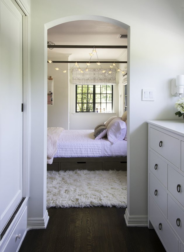 teen bedroom idea for girls with canopy bed and string lights hanging from the ceiling