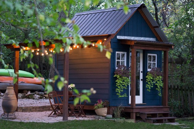 navy blue she shed in backyard surrounded by greenery  with string lights