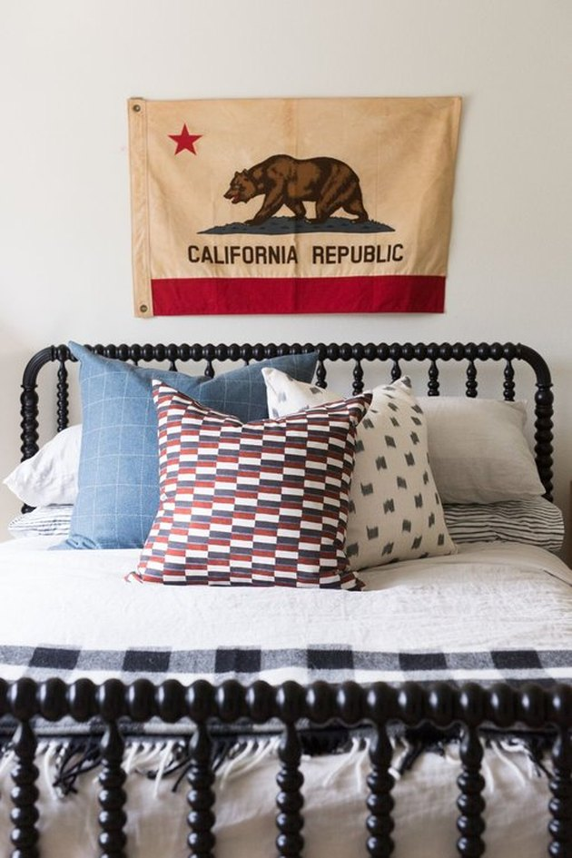 Cali cool teen bedroom idea for girls with vintage flag on wall and black bed frame