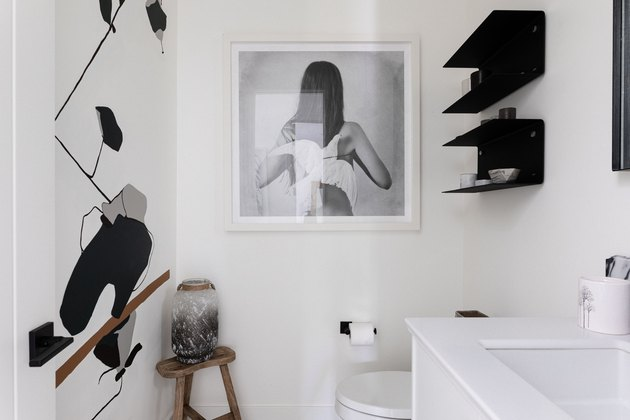 white and black bathroom with single-sink bathroom vanity, toilet and photography wall art