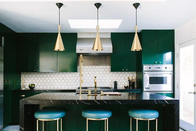 Deep emerald cabinetry and white hexagonal backsplash