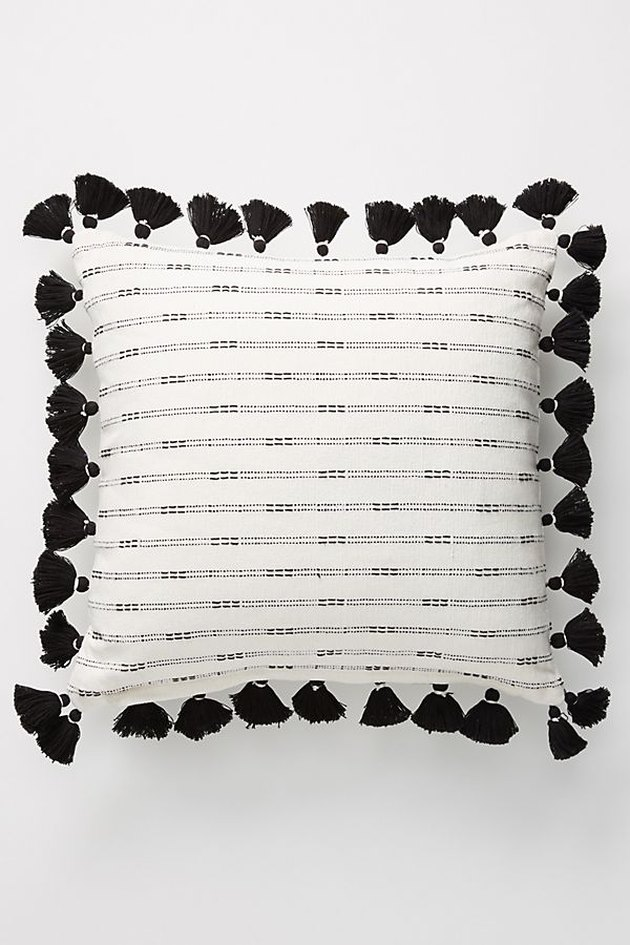 white and black throw pillow with black tassels
