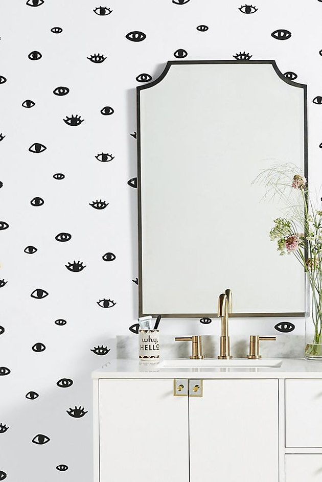 white bathroom with eye wallpaper from Anthropologie