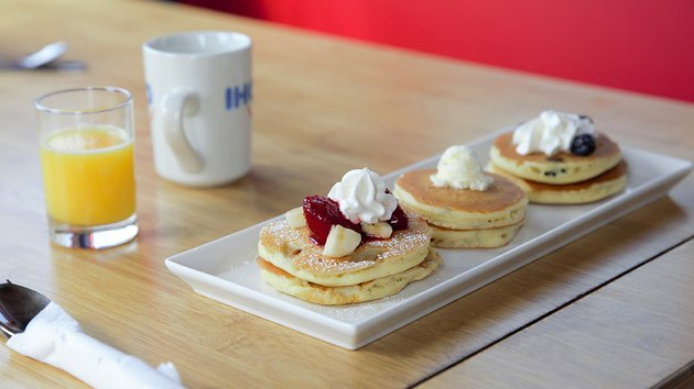 tiny pancakes on a wooden table with orange juice and a mug