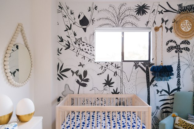 bohemian baby nursery idea with fringe pendant light and animal print wallpaper