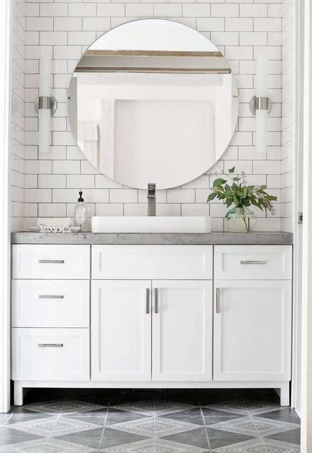 bathroom with concrete countertop and walls with white subway tile