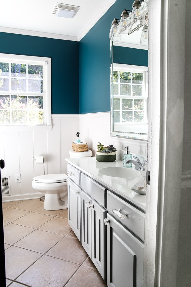 bathroom with teal accent walls and gray cabinet