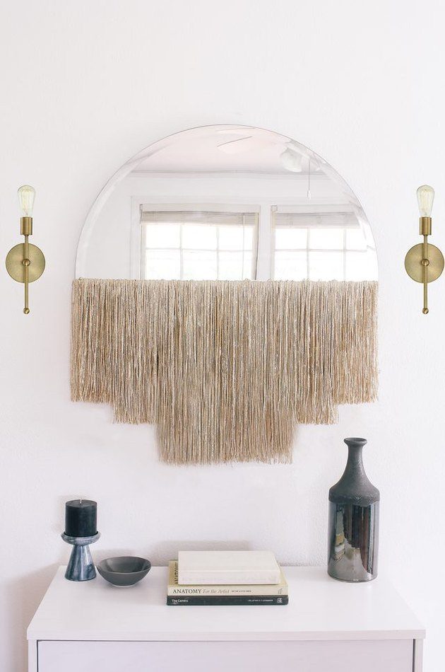DIY fringe mirror between brass wall sconces