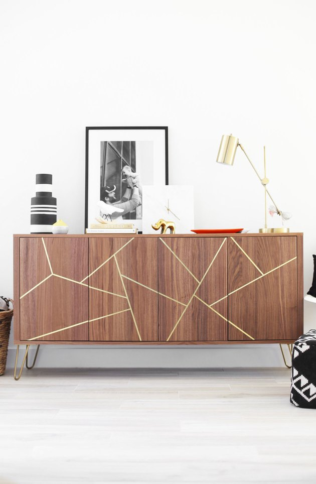 IKEA hack midcentury sideboard with brass inlay detailing topped with artwork and decorative accents