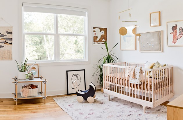 bohemian baby nursery idea with hanging mobile above crib and gallery wall