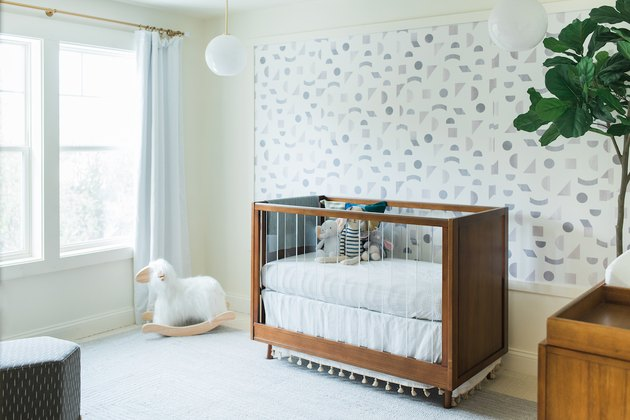 white and gray modern nursery idea with walnut furniture and statement wall