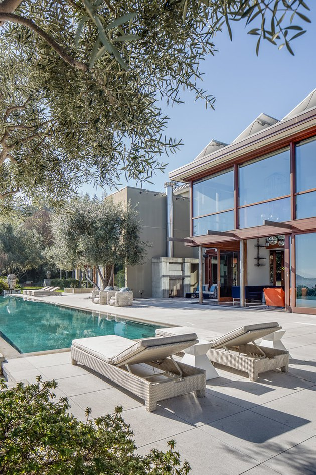 Midcentury backyard pool design with midcentury furniture and linear design accents