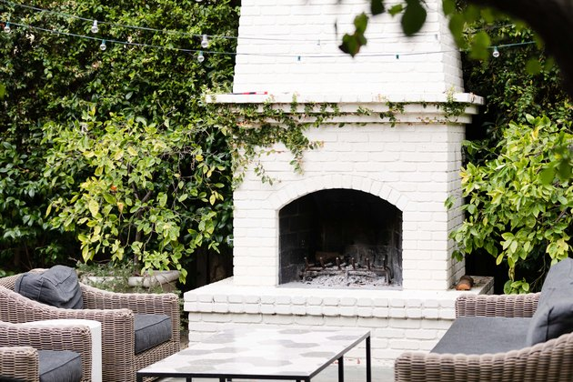 Fireplace on patio with patio chairs and coffee table