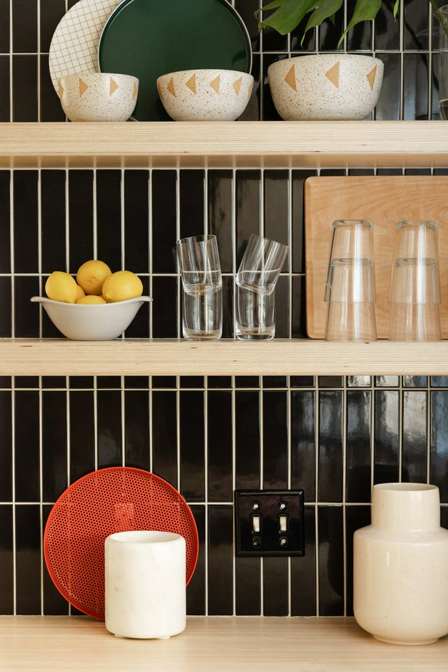 Close up of open shelving and tile work in kitchen, with wood shelves and black tile.