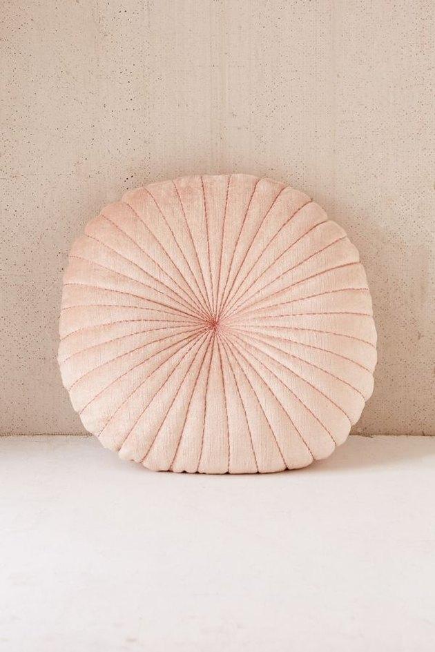 Blush-colored round velvet throw pillow