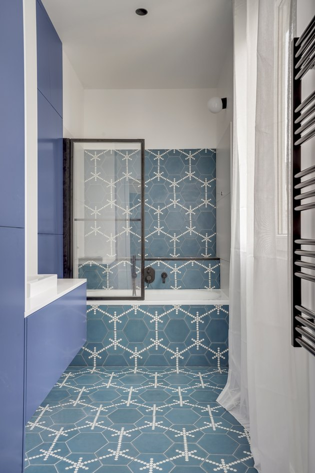 blue and white tile bathroom with black trim glass partition and black shower fixtures