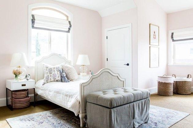 розовая детская спальня с римскими шторами на окнах и стеганой скамейке