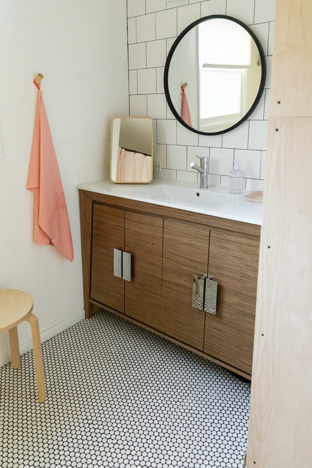 An updated bathroom with large circle mirror and small floor tile.