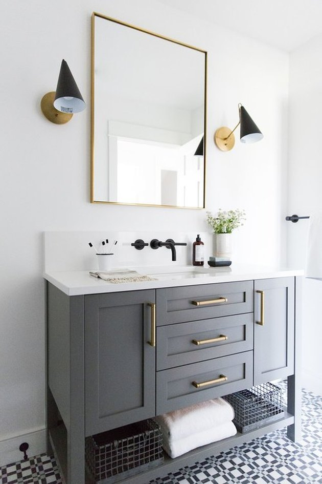 bathroom with gray vanity cabinet and patterned floor tile
