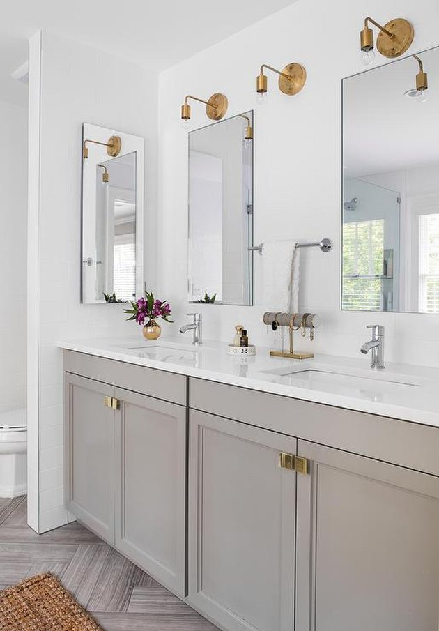 warm gray vanity cabinet with gold fixtures