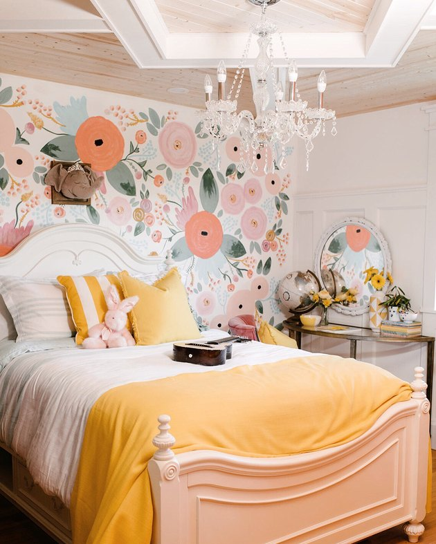 yellow kids bedroom idea with floral accent wall and yellow bedding
