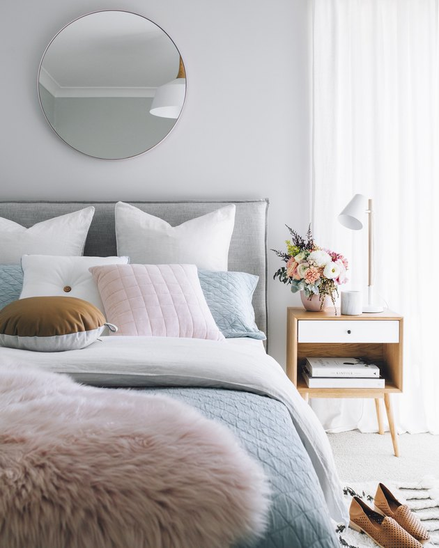 Pastel bedding and bright wood nightstand