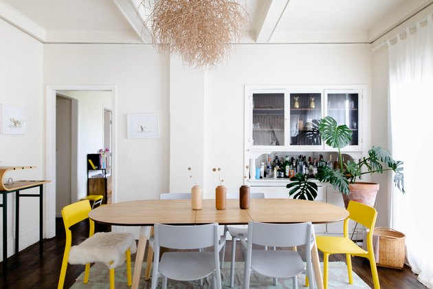 dining room space with wood table and gray and yellow chairs
