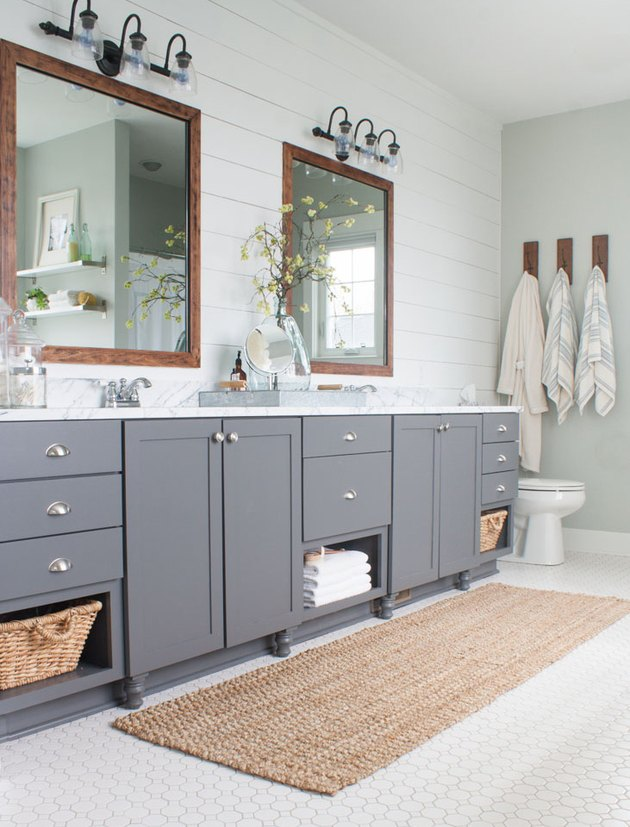 farmhouse bathroom with shiplap wall and gray vanity cabinet