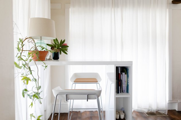white stools and table with plant and lamp nearby