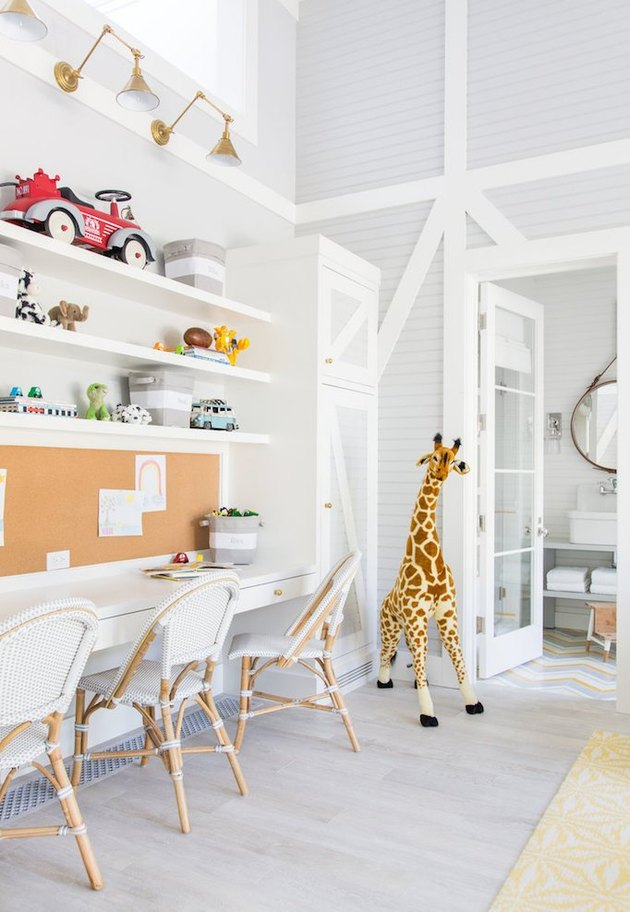 Large kids' bedroom desk area in all-white with farmhouse chairs and children's toys