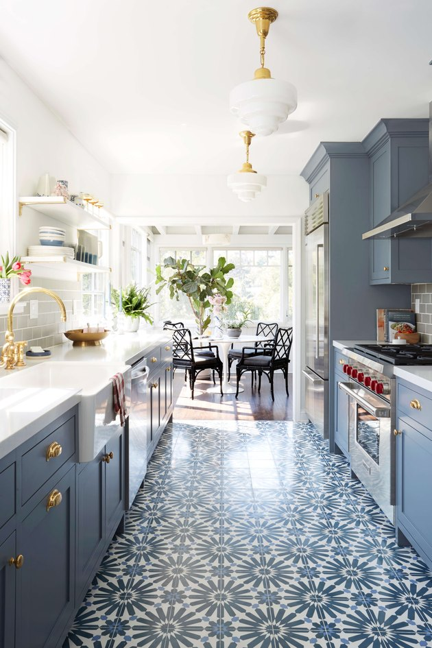 galley kitchen with patterned floor tile and blue cabinets