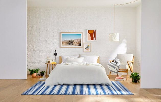 bedroom space with striped blue rug