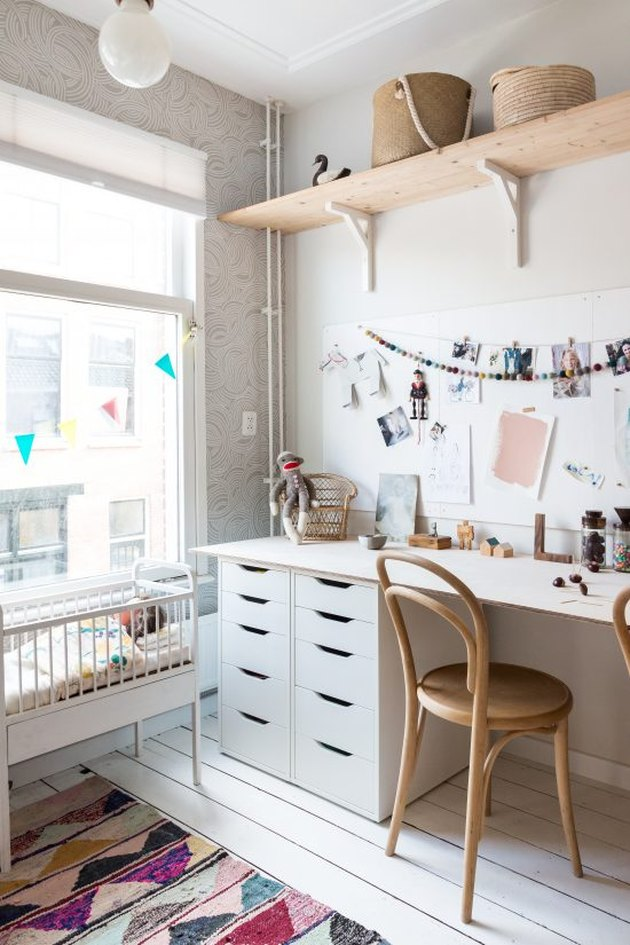 Kids' bedroom desk in all-white palette with pink accents and Scandinavian furniture