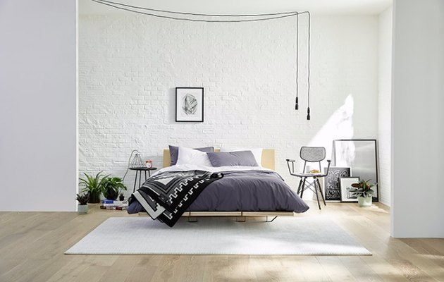 bedroom space with dark sheets and hanging light fixture