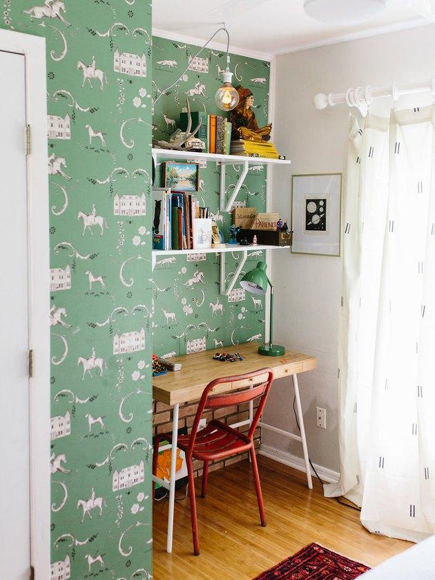 Kids' bedroom desk with green patterned wallpaper and vintage decor