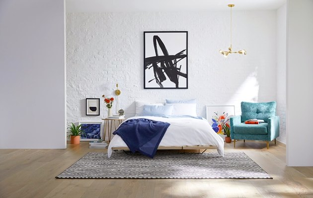 modern glam bedroom with white walls and artwork, blue  chair nearby