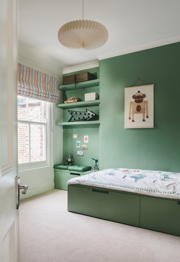 green kids bedroom idea with green wall, shelving, bed and striped Roman shade at window