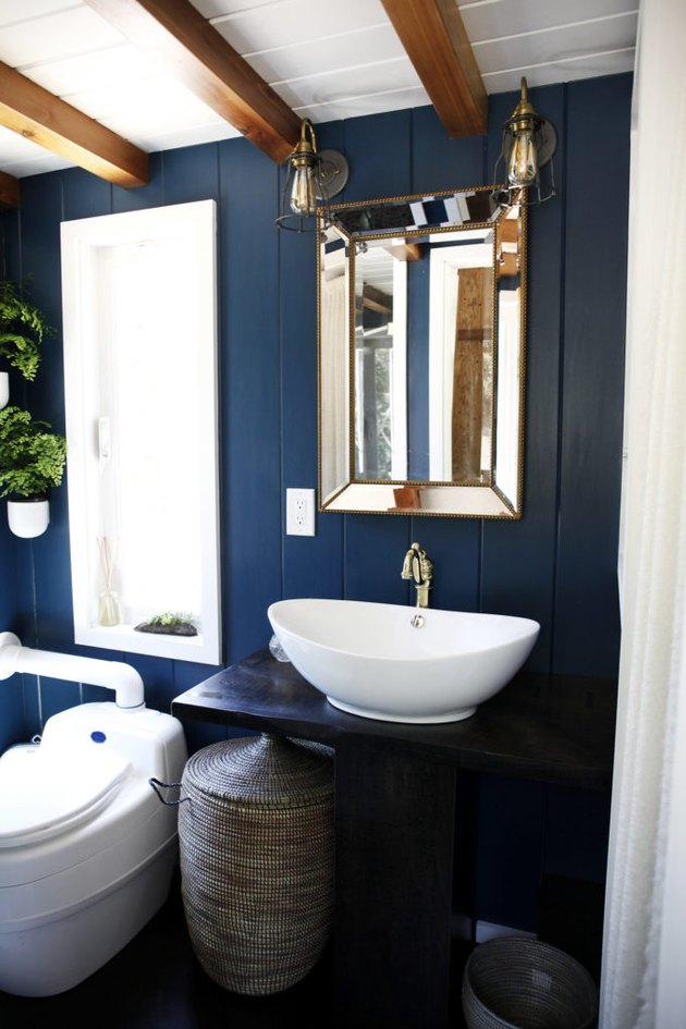 blue bathroom with wood countertop and bowl sink