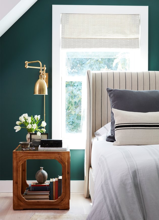 green bedroom with upholstered headboard and brass wall sconces