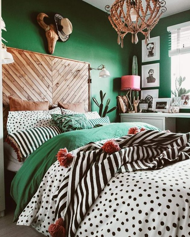 green bedroom with herringbone wood headboard