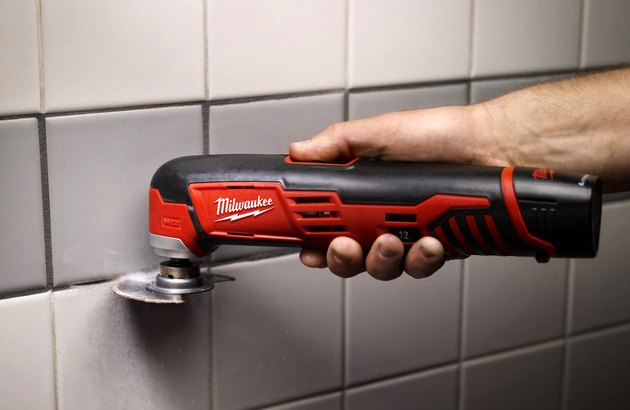 Multi-tool removing grout.