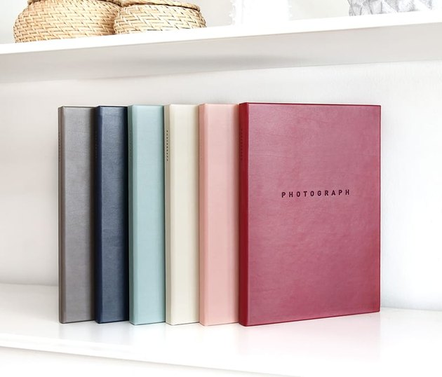 """Leather books in pale rainbow hues with text """"Photograph"""" on cover"""
