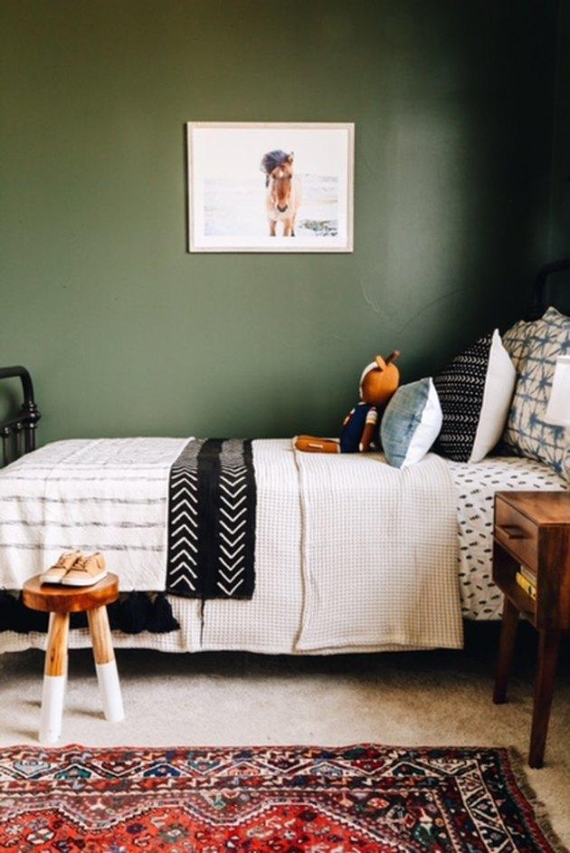 Зеленая детская спальня с мудрыми зелеными стенами и узорными постельными принадлежностями с ковриком на полу